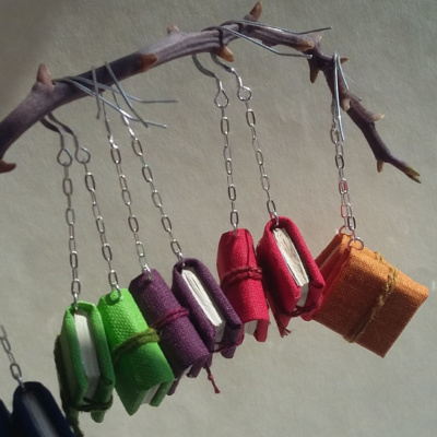 Different colours of book earrings hanging from silver chain from a branch