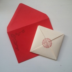 A folded letter paper and red envelope.