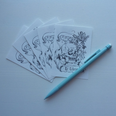 A picture of some bookplates with a pen for size comparison