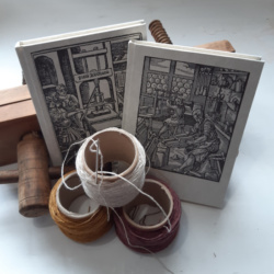 An image showing two hardback notebooks with medieval woodcut images on the cover