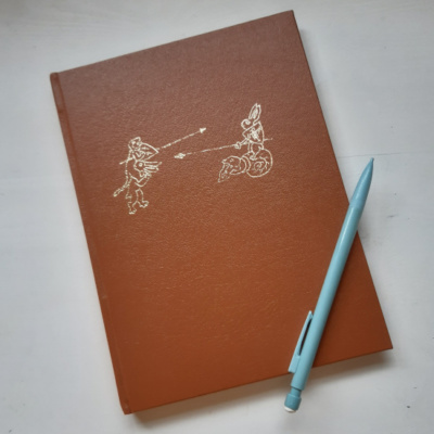 An image of a faux leather hardback notebook with gold image showing a dog on a rabbit jousting a hare on a snail
