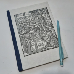 An image of a hardback notebook with blue spine and paper cover showing a woodcut of a 15th century bookbinder at work