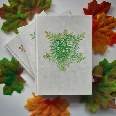 An image of three books with green man image on the cover
