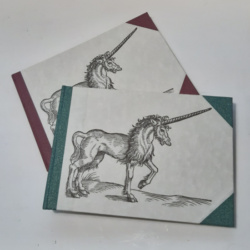 An image of two landscape notebooks with coloured spines and corners and a woodcut of a unicorn on the cover