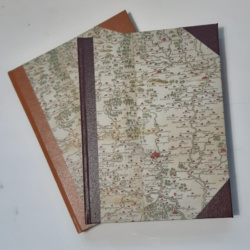 An image of two books with map printed covers and faux leather spine and corners
