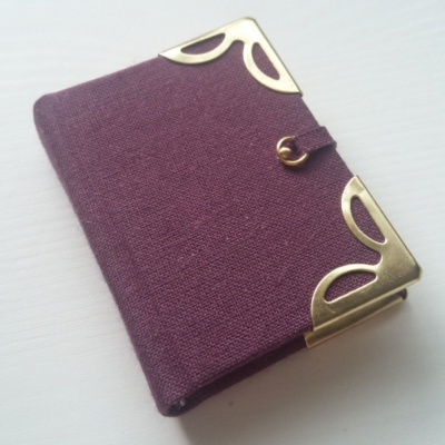 An image of a purple miniature book with gold coloured metal corners and a clasp
