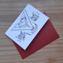 """A small pamphlet notebook resting on a red envelope. The notebook features a picture of an open book with pages turned into a heart shape, and a banner surrounded by roses that reads """"Bound With Love"""""""