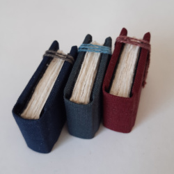 Three miniature books with rough edged text block and linen ties holding them shut.