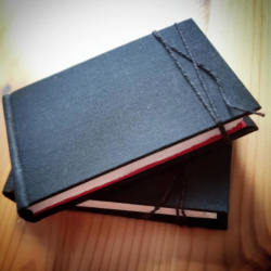 Two black sketchbooks