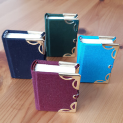 Four miniature books with gold corners and clasps