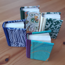 Four different miniature books with cloth spines and paper covers