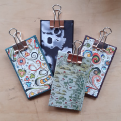 A grouped shot of 4 different designs of clipboards, one with a map image, one swirls with purple, one swirls with green, and one black with white stylised skulls,. They all have rose gold clips.
